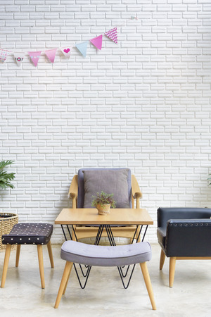 dining table and chairs: cozy sofa corner in industrial and scandinavian style. sofa is in modern style and made with wood. Background is white painted brick Stock Photo