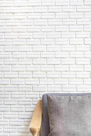 cozy sofa corner with white brick wall in industrial style. Sofa is made with handmade fabric and wood in scandinavian style Reklamní fotografie