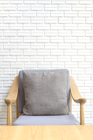 dining table and chairs: cozy sofa corner with white brick wall in industrial style. Sofa is made with handmade fabric and wood in scandinavian style Stock Photo