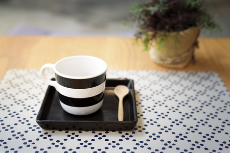 Well designed coffee cup on a wooden table in cafe decorated in industrial style Reklamní fotografie