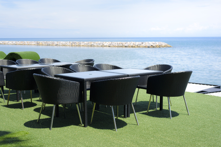 dinner table set made by weaving in black, by the beach in summer under blue sky