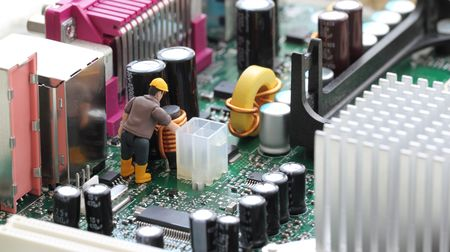 Macro photograph of a computer motherboard and a tiny toy engineer fixing something, concept.