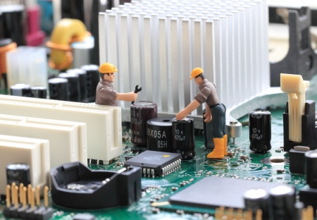 Macro photograph of a computer motherboard and two tiny toy engineers fixing something, concept.