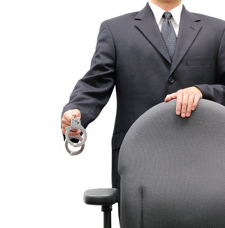 Business man standing behind an office chair holding a pair of handcuffs, isolated on a white background. photo