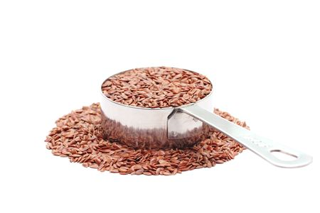 laxative: Macro photo of a quarter cup of flax seeds isolated on a white background. Stock Photo
