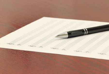 Blank staff paper and mechanical pencil on a wooden desk. Stockfoto