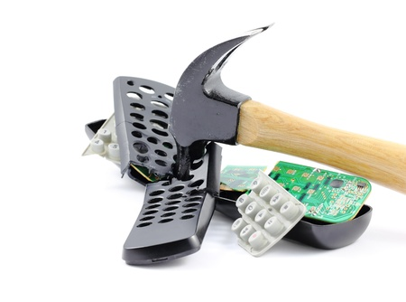 A hammer smashing a television remote control, isolated on a white background.
