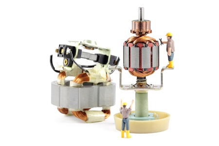 Macro photograph of a disassembled electric motor being worked on by two tiny toy engineers, concept. Stock Photo