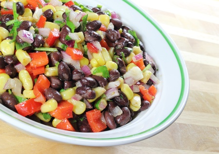 bönor: Southwest Black Bean Salad in a bowl sitting on a table. Stockfoto