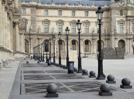 street lamps: A row of lamps along a path in a courtyard in Paris, France.