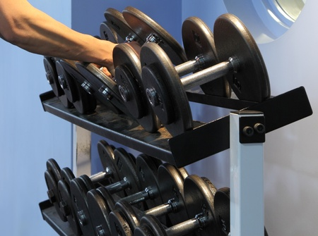 Two dumbbells being lifted from the rack. photo
