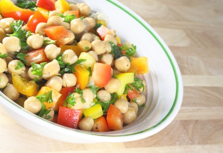 side salad: Chick pea salad in a bowl sitting on a wooden table.