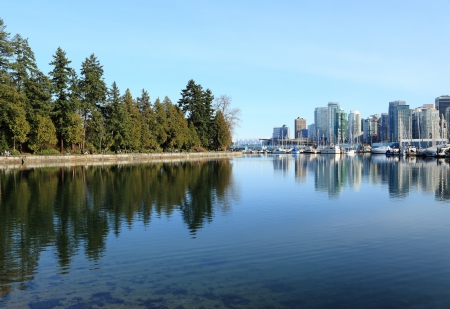 port stanley: View of Stanley Park juxtaposed by a view of downtown Vancouver
