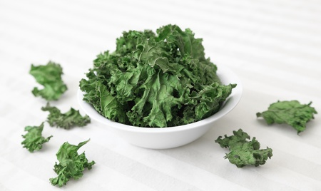 A bowl of home-made kale chips sitting on a table.