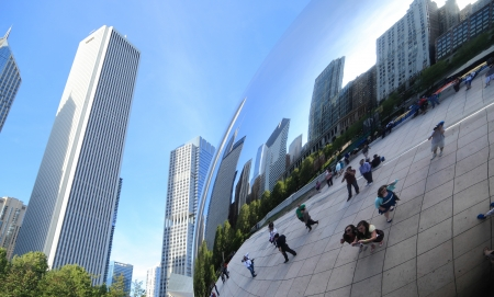 distort: Chicago, Illinois, USA - May 16, 2013  People gather at Cloud Gate to take pictures of themselves and the Chicago skyline reflected on its surface