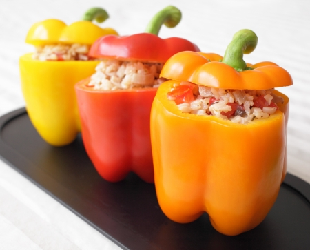 A colorful trio of bell peppers stuffed with rice, mushrooms, and tomatoes
