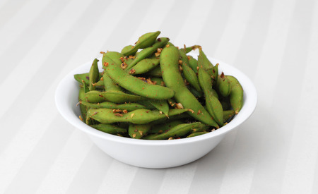 edamame: Spicy Edamame - Cooked and spiced soybean pods in a white bowl