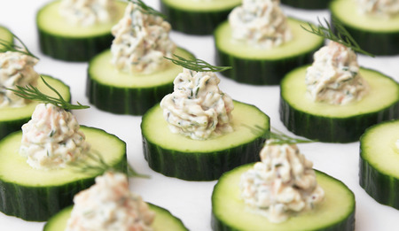 repeated: Salmon mousse served on cucumber slices, garnished with dill