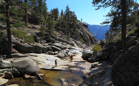watershed: YOSEMITE NATIONAL PARK - SEP 21: Two hikers explore the dry, rocky creek bed of Yosemite Creek near the edge of Upper Yosemite Fall on Sep 21, 2015 at Yosemite National Park.