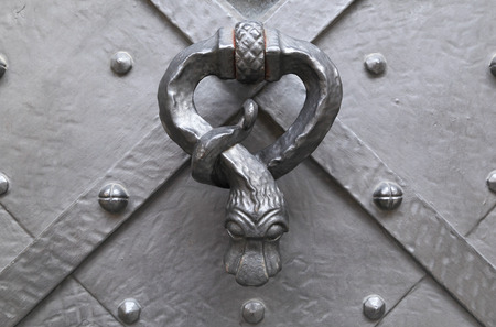summoning: Antique metal door knocker in the shape of a serpent affixed to an antique metal door. Stock Photo