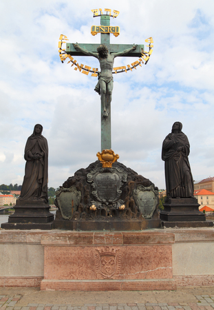 adorn: Situated on the north side of Charles Bridge, the Crucifix and Calvary is one of the many statues that adorn this historic bridge in Prague, Czech Republic. Stock Photo