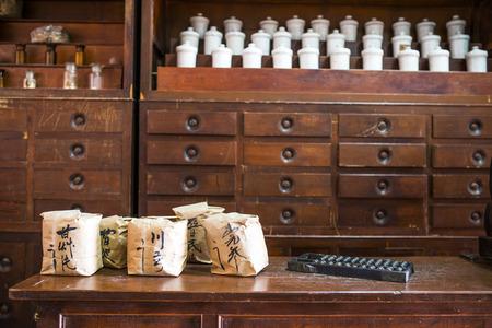 medicina tradicional china: Las hierbas chinas utilizadas en la colocaci�n de los tarros y cajones, papel de embalaje de la fuente es el nombre de la medicina Foto de archivo
