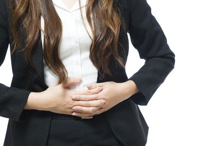 stomach pain: Young businesswoman having back and stomach pain