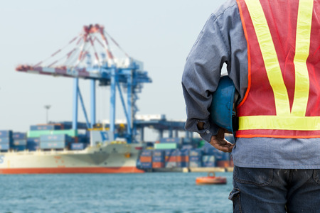 commercial docks: Harbor dock worker talking on radio with ship background Stock Photo