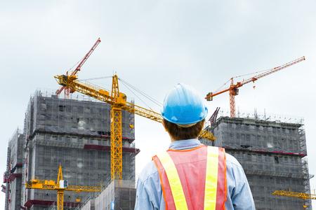 chantier de construction de l'emplacement de la vérification des travailleurs avec la grue sur le fond