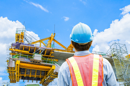 construction worker: construction worker checking location site with crane on the background