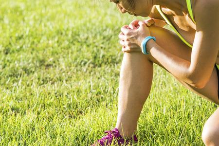 Running sport letsel - gedraaide gebroken enkel. Vrouwelijke atleet loper aan te raken been in pijn als gevolg van verstuikte enkel. Stockfoto