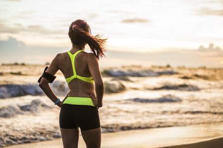 fitnes: młoda kobieta, zdrowy tryb życia działa na wschód słońca plaży