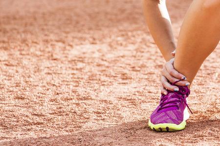 mujer deportista: Ejecución de una lesión deportiva - torció el tobillo roto. Mujer corredor atleta tocar pie en el dolor debido a esguince de tobillo.