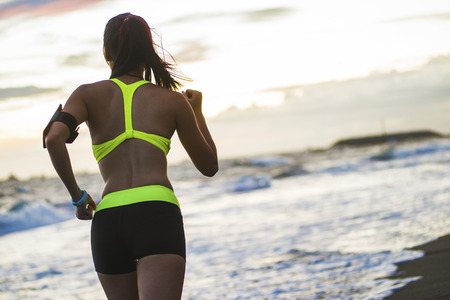 young healthy lifestyle woman running at sunrise beach Stock Photo