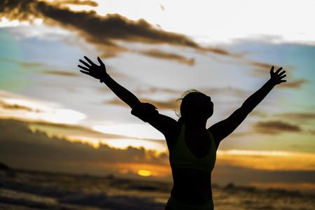 sterk vertrouwen vrouw open armen onder de zonsopgang bij kust