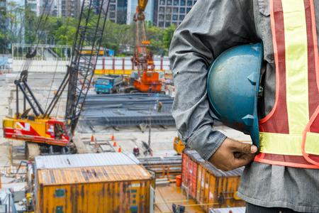 travailleur: travailleur de la construction de v�rifier l'emplacement place avec une grue sur le fond Banque d'images