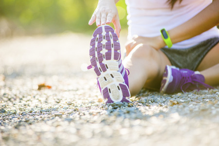 armband: young fitness woman runner stretching legs before run
