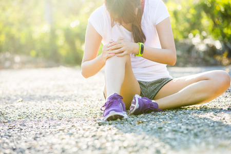 human knee: Runner sport knee injury. Woman in pain while running in park