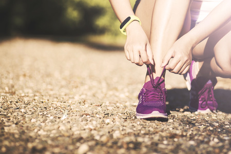 shoelaces: young woman in fitness wear tying shoelaces outdoors