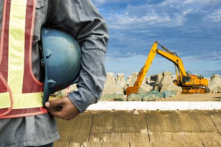 travailleur de la construction de vérifier l'emplacement place avec une grue sur le fond Banque d'images