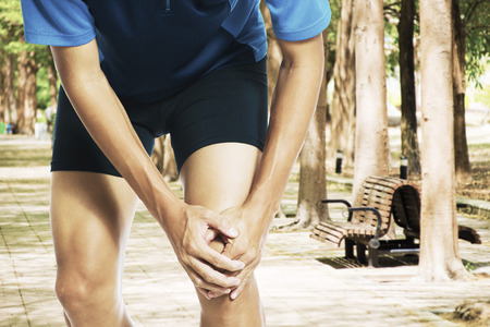 Male athlete runner touching foot in pain due to sprained ankle Stock Photo