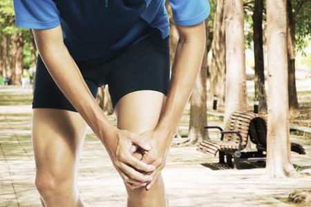 Mannelijke atleet loper aan te raken been in pijn als gevolg van verstuikte enkel Stockfoto