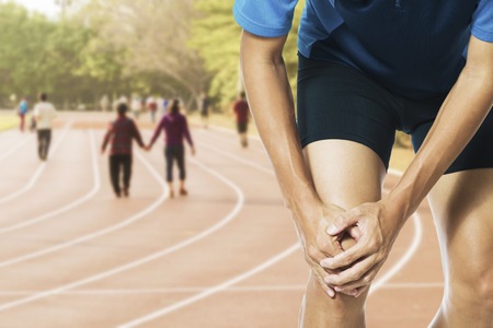sprained joint: Male athlete runner touching foot in pain due to sprained ankle Stock Photo