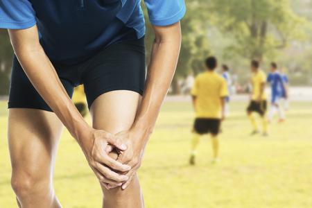 Male athlete runner touching foot in pain due to sprained ankle Banque d'images