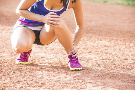 coureur: coureur avec blessure � la cheville d�tient pied pour r�duire la douleur