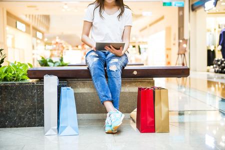 chicas comprando: Mujeres felices con bolsas de compras y ver tel�fono Foto de archivo