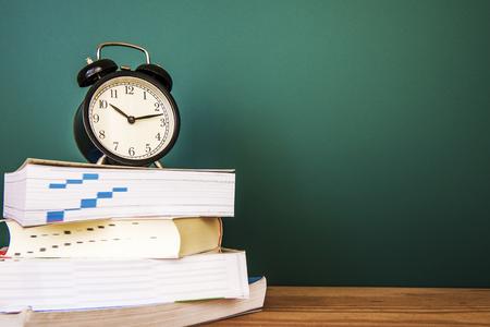 green tone: Retro Alarm clock on text books, vintage green tone