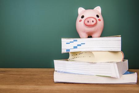 Piggy bank sur le dessus de livres avec tableau, le coût de l'éducation thème