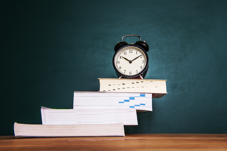 elementary education: Books and clock on a green background Stock Photo