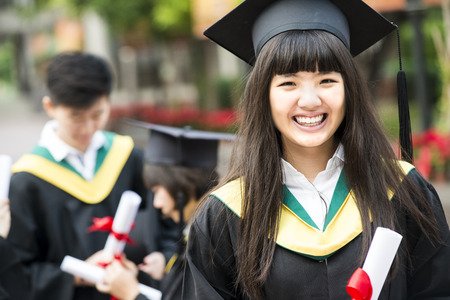 graduation cap and diploma: Group of successful students on their graduation day Stock Photo
